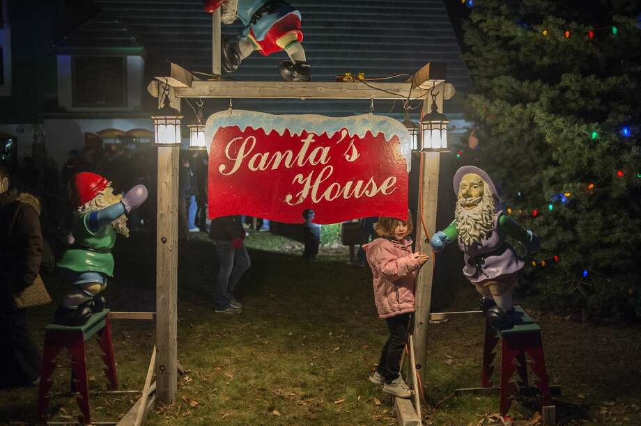 Five-year-old Elaena Austin of Midland plays on the Santa House sign while waiting to enter the house after the annual Midland County Courthouse Lighting Ceremony Tuesday evening. Photo: Brittney Lohmiller/Midland Daily News/Brittney Lohmiller