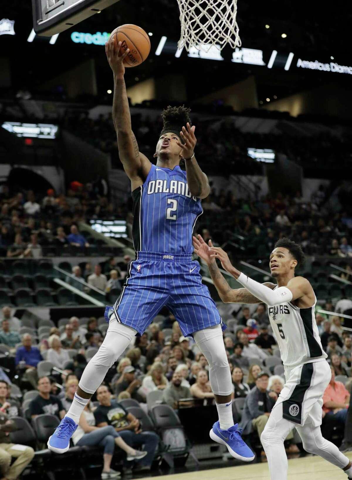 Orlando Magic guard Elfrid Payton (2) scores past San Antonio Spurs guard Dejounte Murray (5) during the first half of a preseason NBA basketball game, Tuesday, Oct. 10, 2017, in San Antonio. (AP Photo/Eric Gay)