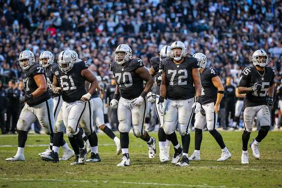 The Oakland Raiders offensive linemen walk through the field during a game against the Carolina Panthers which ended in a Raiders victory, of 35-32,  at the Oakland Colliseum, in Oakland, California, on Sunday November 27, 2016.