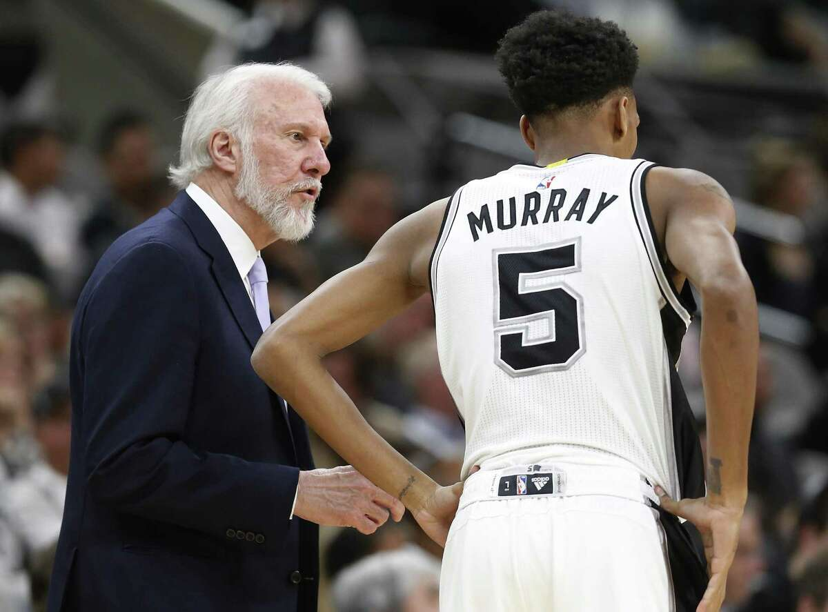 Spurs coach Gregg Popovich talks with Dejounte Murray during their game against the Orlando Magic at the AT&T Center on Nov. 29, 2016.