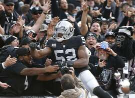 Raiders defensive end Khalil Mack leaps into the welcoming arms of the Black Hole denizens after his interception return for a touchdown in Sunday's win over the Carolina Panthers.