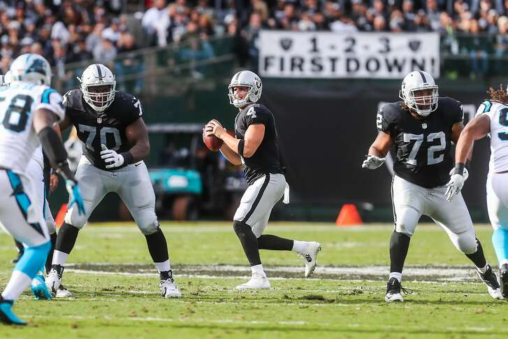 Quarternack Derek Carr (center, #4) prepares to make a pass as his offensive lineman block for him, in a game against the Carolina Panthers, at the Oakland Colliseum, in Oakland, California, on Sunday, Nov. 27, 2016.