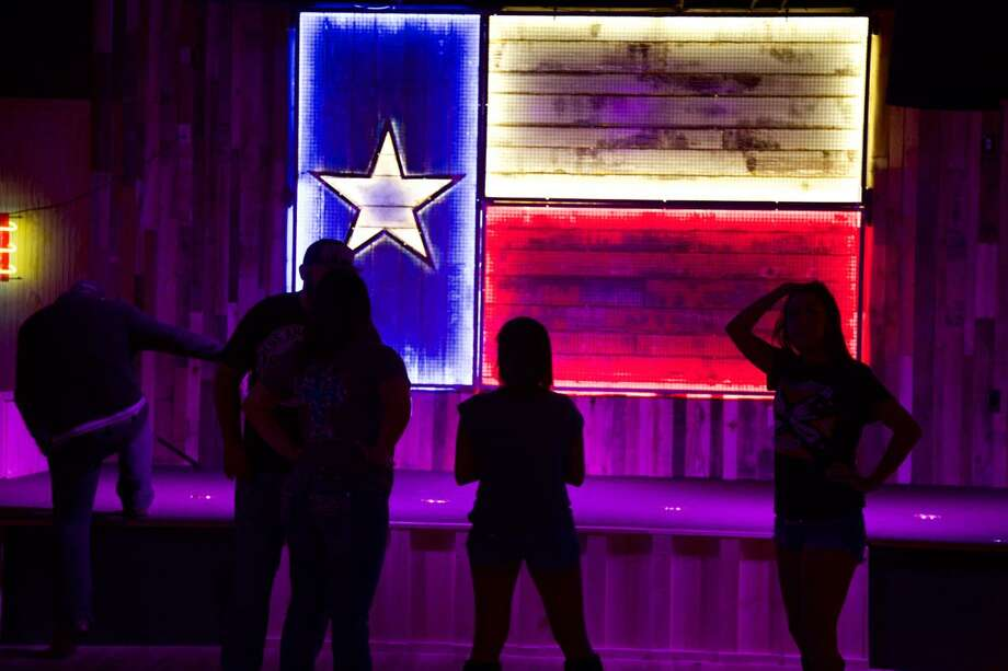 Big Texas Icehouse customers are standing in front of a Texas Flag art piece. Photo: Photos By Xelina Flores /For The Express-News