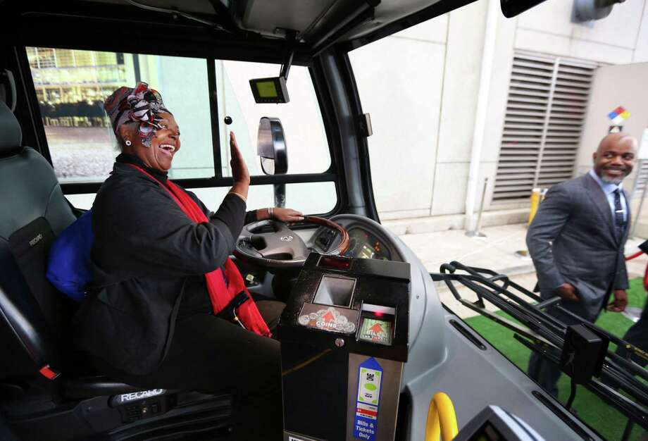 "Janis Scott, known to many Metro employees as ""The Bus Lady,"" waves to Metro board member Troi Taylor, right, as she sits in the driver's seat of the new Proterra battery electric bus that Metro will be using in a pilot program for the next three months, after officials debuted the bus on Nov. 29.  Photo: Houston Chronicle / © 2016 Houston Chronicle"