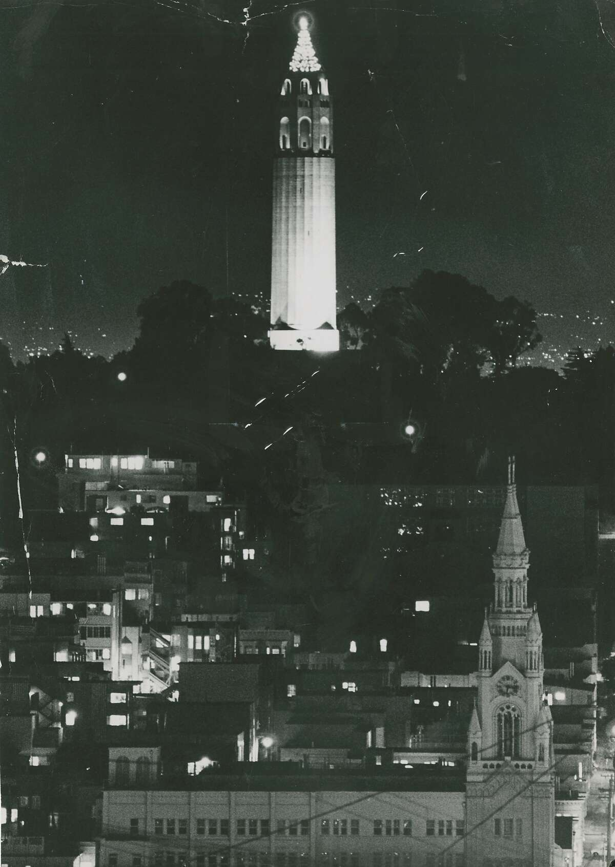 Coit Tower is adorned and lit for Christmas, December 22, 1970. Saints Peter and Paul Church is seen in the foreground.