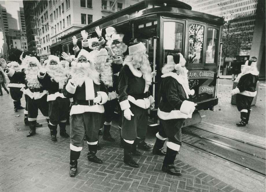 Twenty Santas make their way to San Francisco's Hyatt Regency to attend a training session in 1987. Photo: Frederic Larson, San Francisco Chronicle