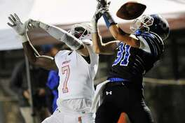 Greenwich defender James Day (7), left, breaks up a second quarter end-zone pass to Darien receiver Timothy Herget during a Class LL game Tuesday night at Boyle Stadium in Stamford.