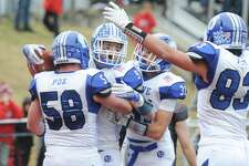 Darien's Finlay Collins, center, celebrates a touchdown with teammates Cord Fox (58), Timothy Herget (31), and Quinlin Fay (83) in Darien's 37-34 win over New Canaan in the Turkey Bowl high school football game at Dunning Stadium in New Canaan, Conn. Thursday, Nov. 24, 2016. New Canaan scored 24 unanswered points to tie the game and force an overtime. In overtime, Darien kicked a field goal to take the lead and forced a New Canaan interception to end the game, setting off a wild celebration as fans stormed the field.