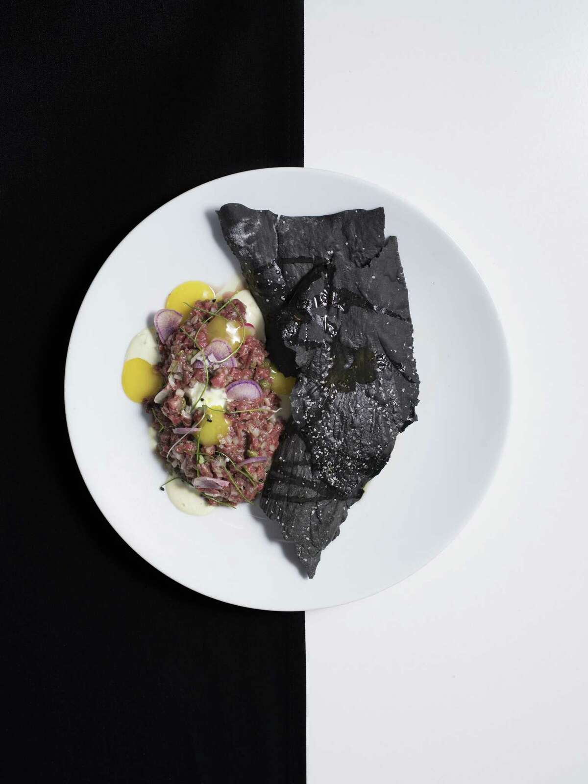 Wagyu tartare with a duck egg custard, garlic aioli and squid ink crackers at Feast.