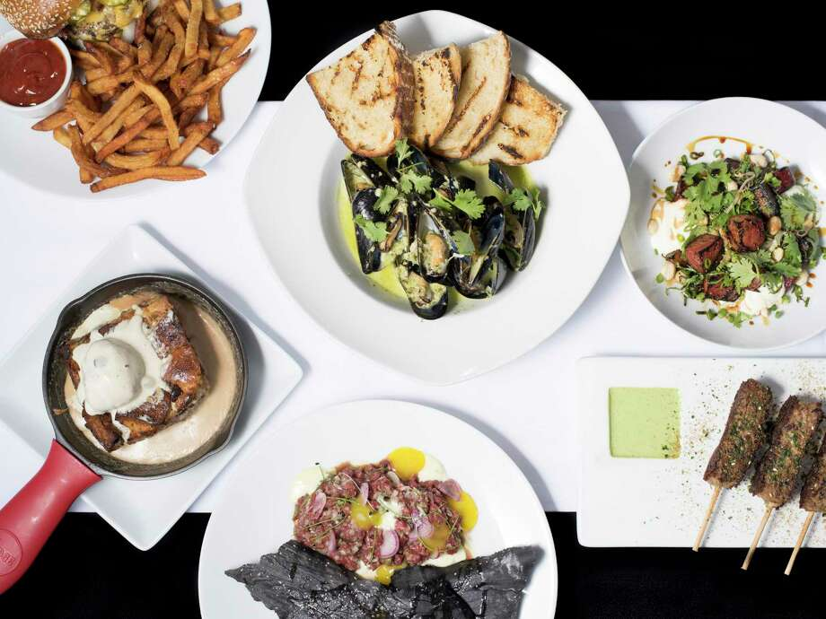 A medley of dishes including a double burger, lamb kebab, beef tartare, grilled chioggia beets, mussels and bread pudding at Feast. Photo: Matthew Busch /For The Express-News / © Matthew Busch