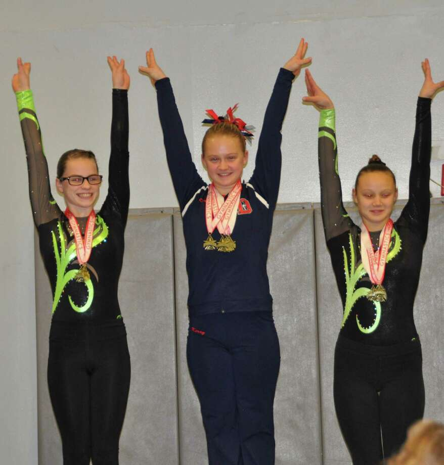 Darien Level 6 gymnast Kerry McDermott (center) placed first on floor and All-Around in her age group at the Lakewood-Trumbull YMCA Harvest Invitational. Photo: Contributed Photo / Darien News contributed