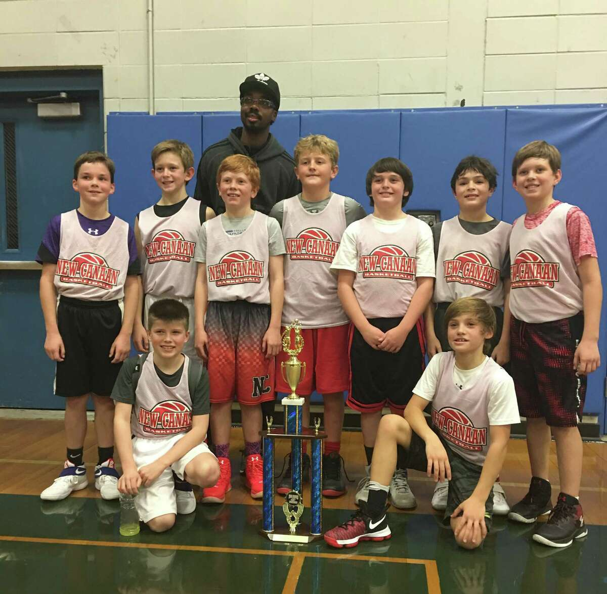 The New Canaan fifth-grade Black team poses with its trophy after winning the Milford Tip-Off Tournament.