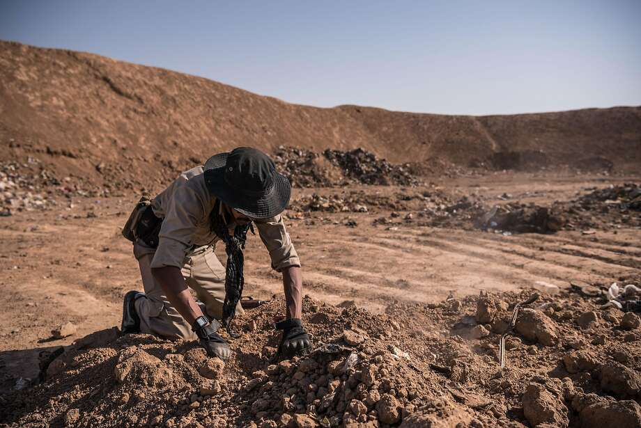 A soldier searches for remains at a mass grave site, a trash dump near Hamam al-Alil, Iraq. The site outside this old spa resort town was the largest mass grave uncovered recently. Photo: SERGEY PONOMAREV, NYT
