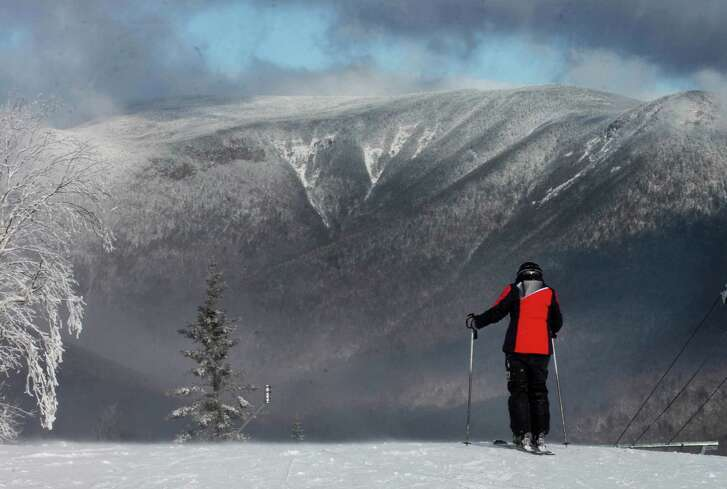 A skier looks out over the White Mountains before skiing on opening day at Loon Mountain ski resort Wednesday, Nov. 23, 2016, in Lincoln,N.H.