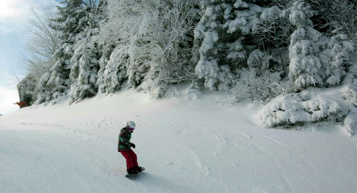 A young snowboarder takes the first run of the season on top of the mountain on opening day at Loon Mountain ski resort.