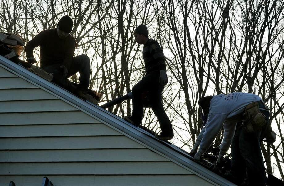A DiGiorgi Roofing & Siding crew at work on a roof in January 2014 in Derby, Conn. Photo: Christian Abraham / Christian Abraham / Connecticut Post