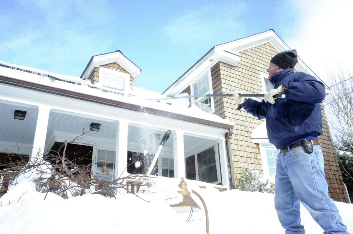 Builder and Greenwich resident Lee Neuberth uses a roof rake to clear snow off his roof in December 2010.