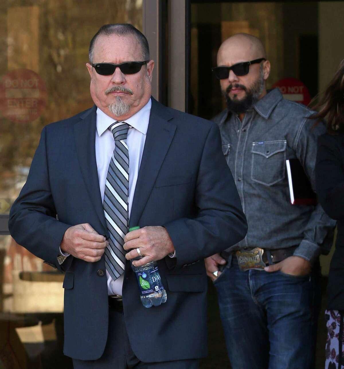 FILE - Bandidos motorcycle club president Jeff Pike, left, exits Wednesday, Nov. 30, 2016 the John H. Wood, Jr. Federal Courthouse in San Antonio. A new indictment, filed Wednesday in San Antonio, added four San Antonio residents, Pike and Bandidos' national vice president John Xavier Portillo as the defendants in the killing of Anthony W. Benesh III.