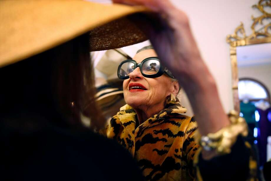 Joy Bianchi helps Allison Thompson try on a hat at Helpers House of Couture in San Francisco. Photo: Scott Strazzante, The Chronicle