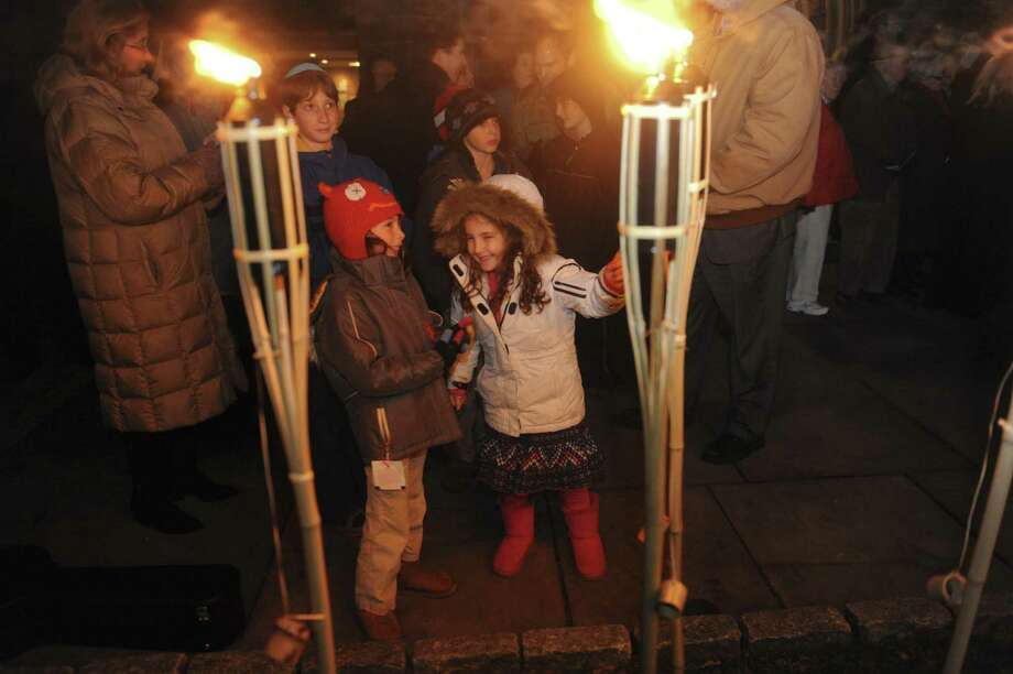 Phoebe Porigow, 6, and Charlotte Falus, 6, look at a Menorah at Temple Sholom and Christ Church Greenwich's an interfaith candle-lighting ceremony at Christ Church in Greenwich in 2012. This year's ceremony is set for 5:30 p.m. Dec. 8 on the front plaza at Christ Church. Photo: Helen Neafsey / Helen Neafsey / Greenwich Time