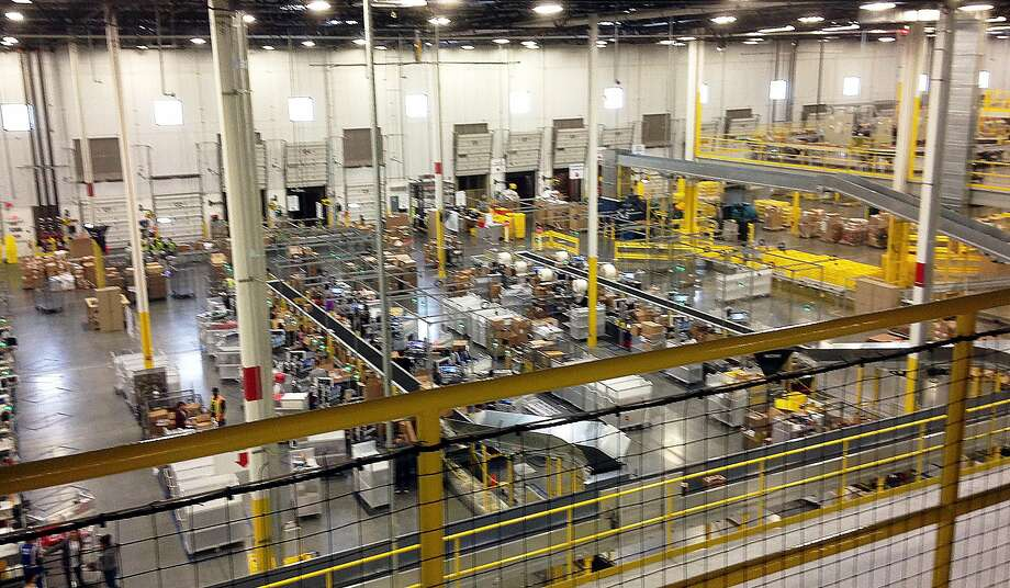One of Amazon's newest distribution centers in Tracy, Calif., is seen during a tour Sunday, Nov. 30, 2014. This Amazon Fulfillment Center opened in 2013 and was refitted to use new robot technology in the summer of 2014. All year Amazon has been investing in ways to make shipping faster and easier to prepare for this holiday season. At this Northern California warehouse the company is employing robotics and other new technology to help workers process the annual onslaught of shopping orders. (AP Photo/Brandon Bailey) Photo: Brandon Bailey, Associated Press