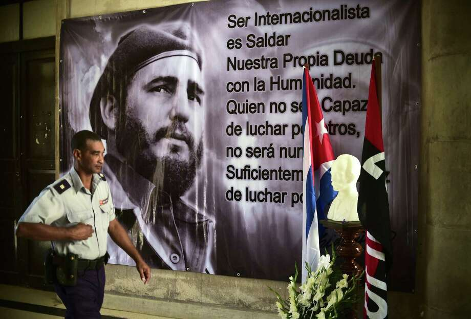 A police officer passes by a portrait of late Cuban revolutionary leader Fidel Castro in Havana. We have the chance to flood Cuba with American ideas and values. Photo: RONALDO SCHEMIDT /AFP /Getty Images / AFP or licensors