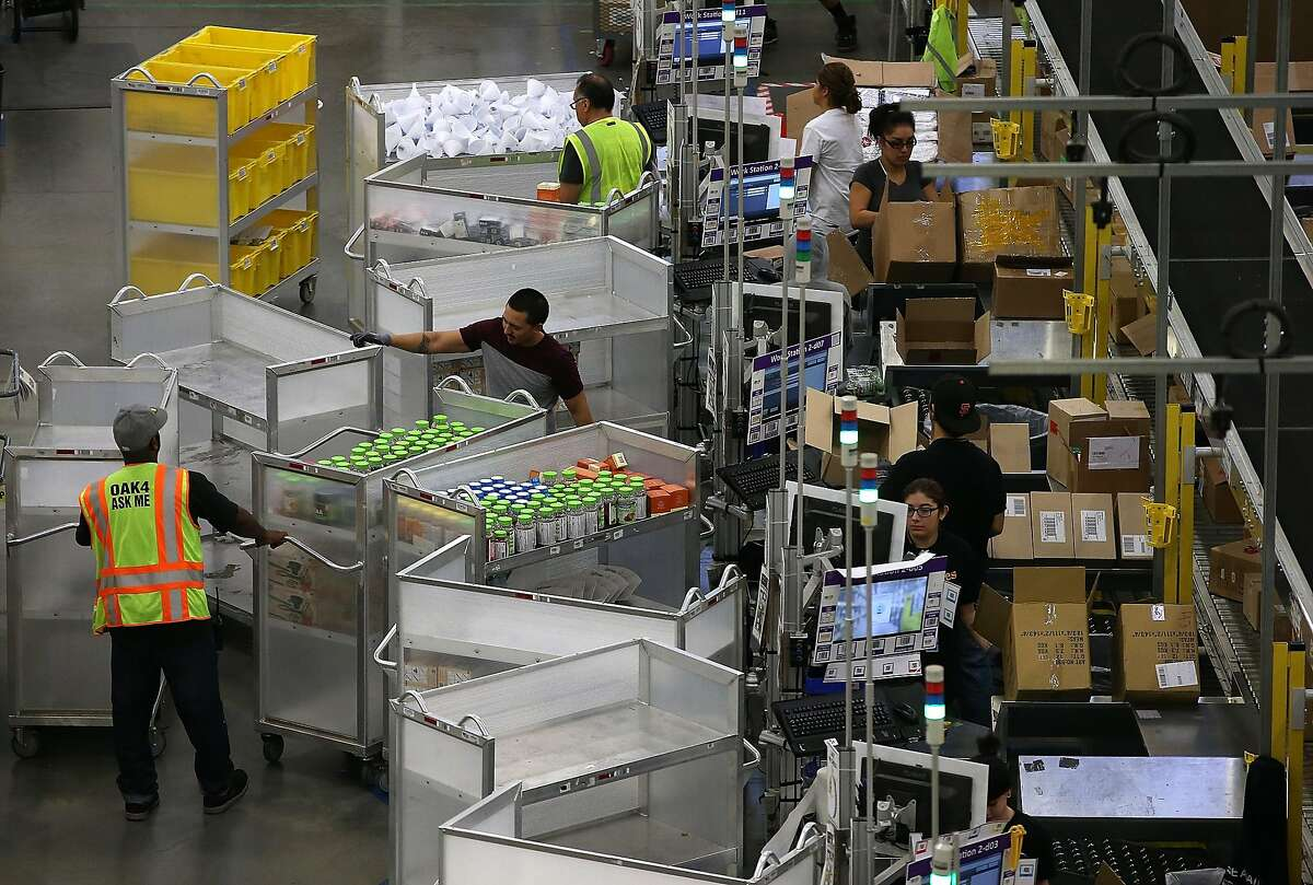 TRACY, CA - JANUARY 20: Amazon.com workers pack orders at an Amazon fulfillment center on January 20, 2015 in Tracy, California. Amazon officially opened its new 1.2 million square foot fulfillment center in Tracy, California that employs more than 1,50