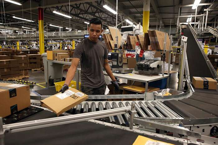 TRACY, CA - JANUARY 20: An Amazon.com worker sorts packages onto a conveyor belt at an Amazon fulfillment center on January 20, 2015 in Tracy, California. Amazon officially opened its new 1.2 million square foot fulfillment center in Tracy, California th
