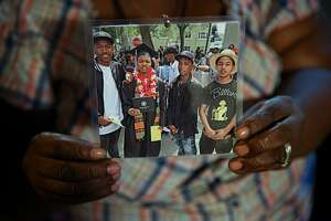 Teresa Jackson holds a photo of her son Roderick Travon Godfrey (second from left), family friend Deante Antonio Miller (right) on Tuesday, Nov. 29, 2016 in Oakland, Calif. Godfrey and Miller, both age 19, were both shot and killed on Monday at approximately 10:15 a.m. on the 700 block of 39th Street, between West Street and Martin Luther King Jr. Way, police said. No suspect was identified or arrested in the killings.
