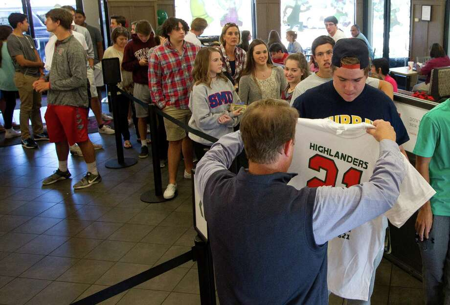 Tyler Matheny purchases a t-shirt to raise money for Grant Milton, a varsity football player at The Woodlands High School, at Chick-fil-A at the Alden Bridge Village Shopping Center Wednesday in The Woodlands. Photo: Jason Fochtman, Staff Photographer / Houston Chronicle