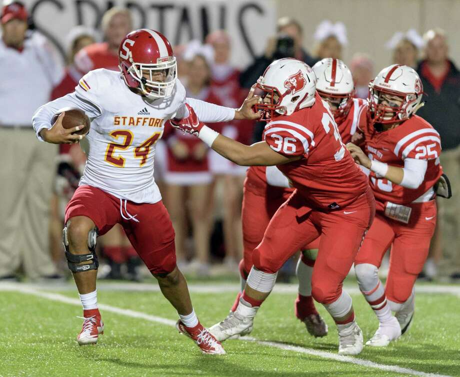 Jalen Pitre (24) of the Stafford Spartans stiff arms Andy Lara (36) of the Bridge City Cardinals in the first half in a high school football Class 4A, Division 1 Regional Semifinal on Friday, November 25, 2016 at Maddry Stadium in Channelview Texas. Photo: Wilf Thorne / © 2016 Houston Chronicle
