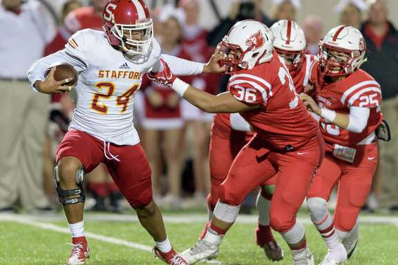 Jalen Pitre (24) of the Stafford Spartans stiff arms Andy Lara (36) of the Bridge City Cardinals in the first half in a high school football Class 4A, Division 1 Regional Semifinal on Friday, November 25, 2016 at Maddry Stadium in Channelview Texas.