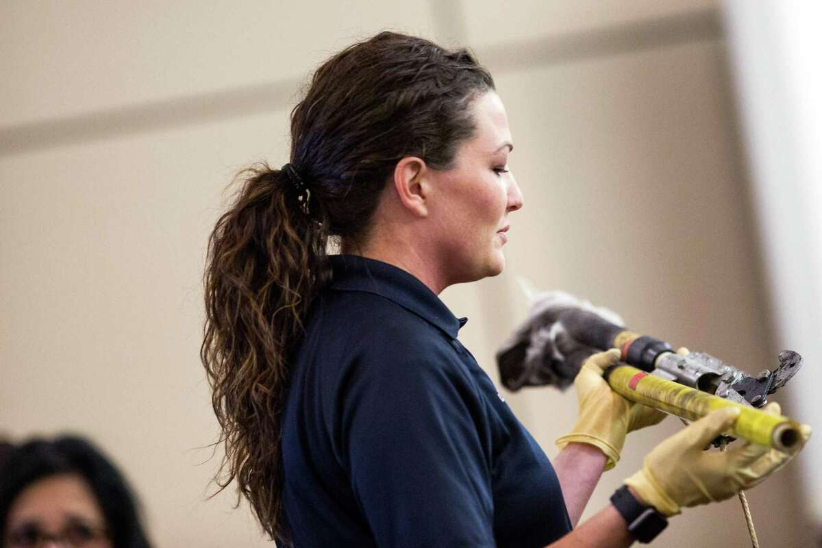 Crime scene investigator Lyndsey Patten examines a tree trimmer submitted as evidence Wednesday in the trial of Michael Scott Quinn. Ray Whitehouse / for the San Antonio Express-News