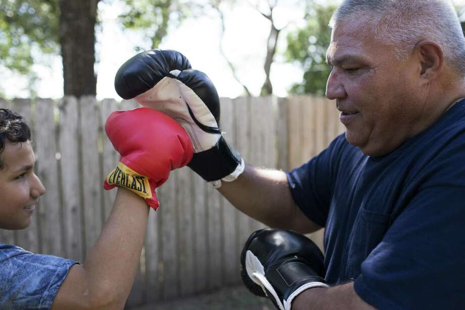 Willie Ruiz, 53, boxes with his son Marco Ruiz, 11, at their home in Alice, Sunday, Oct. 9, 2016. Marco Ruiz is a student who used to receive special education until he was eliminated from the program. Now his parents are trying to get him help he needs. ( Marie D. De Jesus / Houston Chronicle ) Photo: Marie D. De Jesus, Staff / Houston Chronicle / © 2016 Houston Chronicle