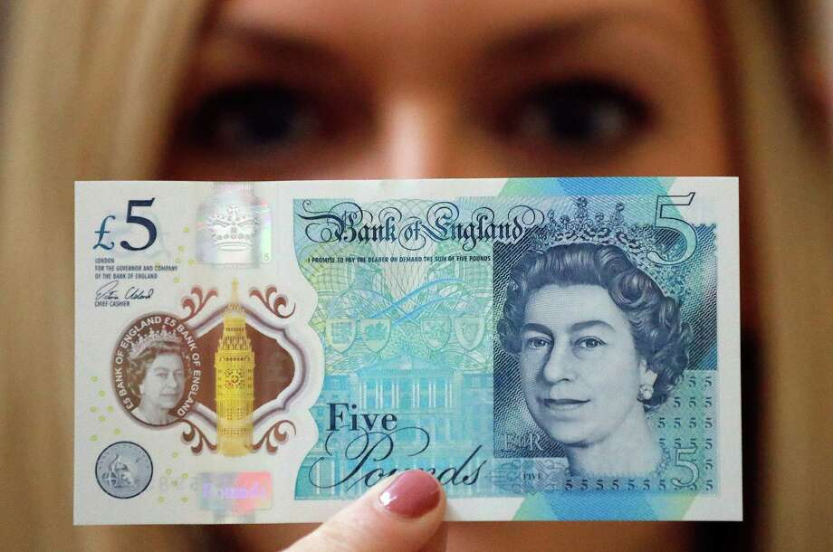 A Bank of England employee shows the new 5-pound note this fall at the Bank of England Museum in London. Tallow was used in the base of the polymer notes.  Photo: Frank Augstein, STF / ap