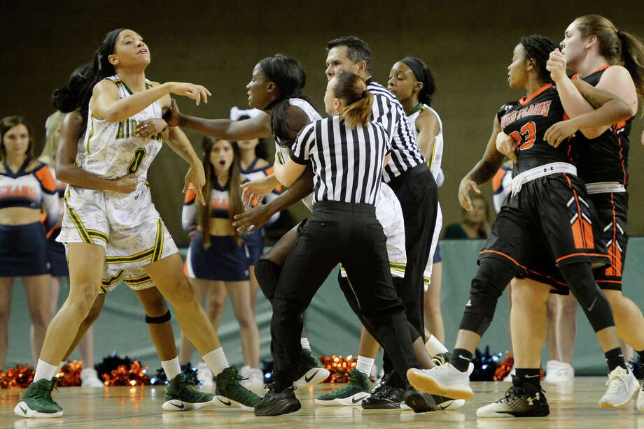 Midland College's Alexandrea Washington (11) holds back teammate Janea Bunn (0) after Bunn was involved in an altercation with South Plains' Brittany Smith (23, far right) on Wednesday, Nov. 30, 2016, at Chaparral Center. Bunn and Smith were both ejected from the game along with Midland College's Teneshia Dixon. James Durbin/Reporter-Telegram Photo: James Durbin