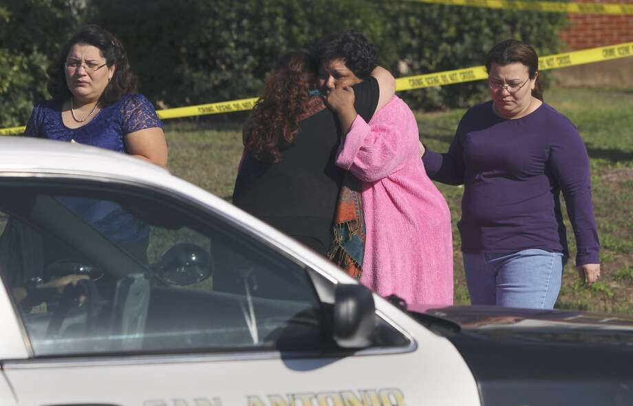 Christina Herrera (center, in light-colored robe) is consoled at the scene of a March 2, 2011, apartment fire where her daughter Esmeralda Herrera died. Photo: San Antonio Express-News / File Photo / SAN ANTONIO EXPRESS-NEWS (Photo can be sold to the public)