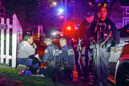 Police stand by a distraught woman at the scene where a Tacoma Police officer was shot while responding to a domestic call in East Tacoma, Wash., Wednesday, Nov. 30, 2016. KCPQ-TV reports an officer was taken to a Tacoma hospital Wednesday after the incident at about 5:30 p.m. (Peter Haley/The News Tribune via AP)