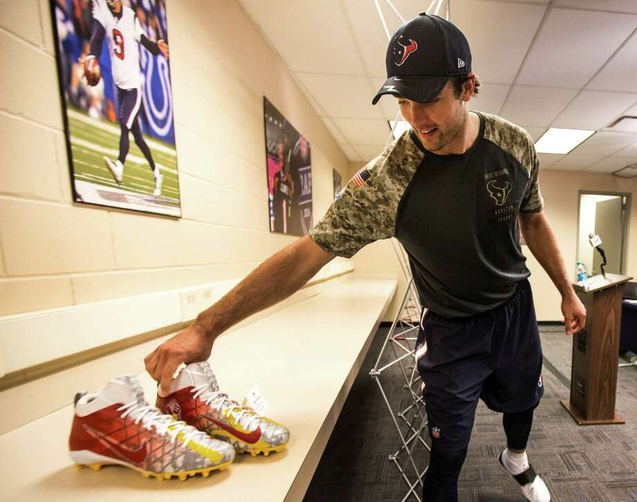 Texans quarterback Brock Osweiler on Wednesday admires his cleats designed by Nike that support the Ronald McDonald House. Osweiler's cause is childhood cancer. Photo: Brett Coomer, Staff / © 2016 Houston Chronicle