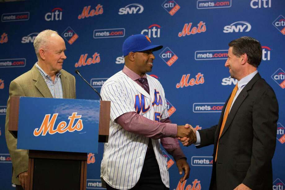 Yoenis Cespedes shakes hands with New York Mets COO Jeff Wilpon, right, while on stage with Mets general manager Sandy Anderson during a news conference announcing his new $110 million, four-year contract with the Mets at Citi Field on Wednesday, Nov. 30, 2016, in New York. Cespedes' contract is for $22.5 million in 2017, $29 million in each of the following two seasons and $29.5 million in 2020. (AP Photo/Kevin Hagen) ORG XMIT: NYKH102 Photo: Kevin Hagen / FR170574 AP