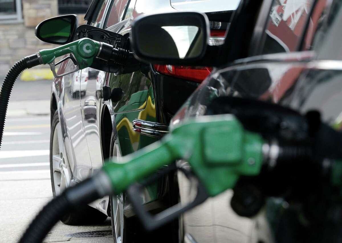 FILE - In this June 30, 2016, file photo, gas is pumped into vehicles at a BP gas station in Hoboken, N.J. The Obama administration has decided not to change government fuel economy requirements for cars and light trucks despite protests from automakers. (AP Photo/Julio Cortez, File)