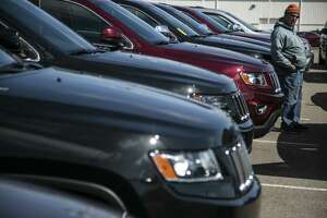A potential car buyer views a Jeep SUV in Troy, Mich. The EPA says its requirements will increase the new-vehicle fleet's average gas mileage requirement from 34.1 miles per gallon this year while cutting carbon pollution and saving drivers billions at the pump.