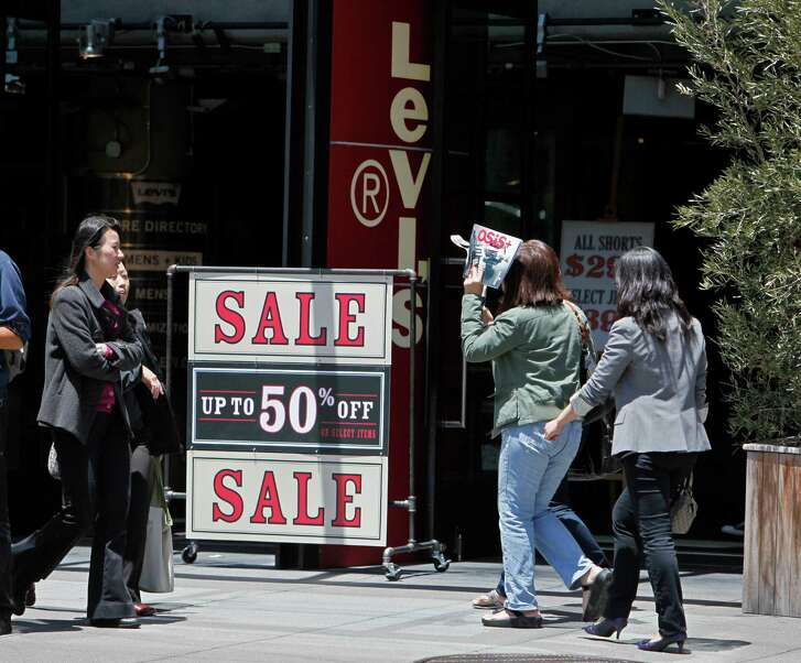 FILE - In this June 1, 2010, file photo, people walk by a sale sign at the entrance of the Levi's store on Union Square in San Francisco. Levi Strauss & Co. President and CEO Chip Bergh asked customers and employees in an open letter posted on LinkedIn Nov. 30, 2016, not to bring guns into its stores, offices or facilities, even in states where it's legal. (AP Photo/Eric Risberg, File)