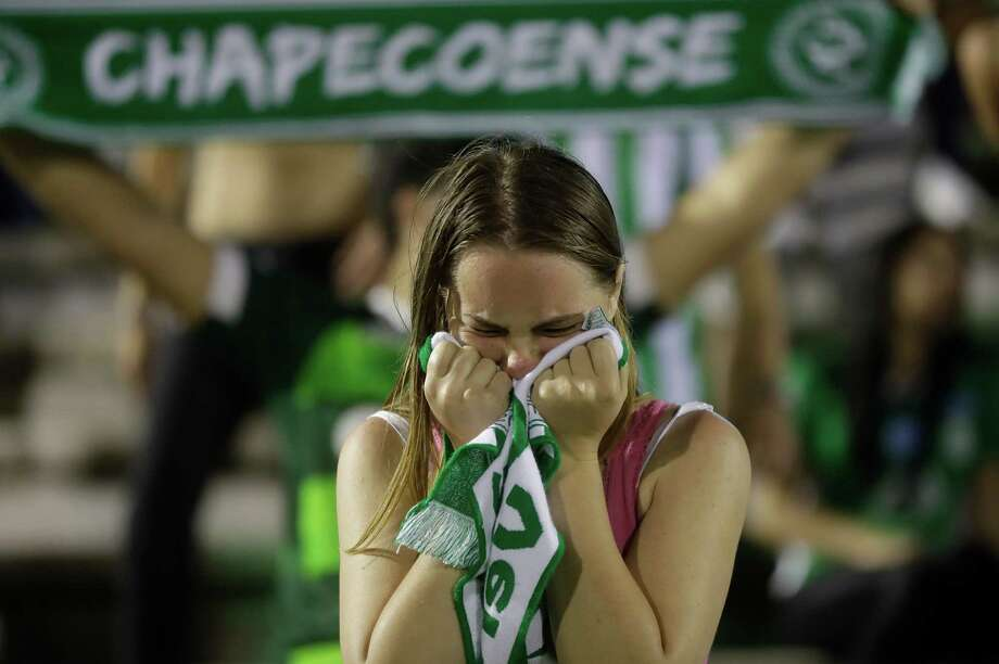 A fan of Brazil's soccer team Chapecoense mourns during a gathering inside Arena Conda stadium in Chapeco, Brazil, Tuesday, Nov. 29, 2016. A chartered plane carrying the Brazilian soccer team Chapecoense to the biggest match of its history crashed into a Colombian hillside and broke into pieces on Tuesday, killing most passengers, Colombian officials said. (AP Photo/Andre Penner) ORG XMIT: XAP135 Photo: Andre Penner / Copyright 2016 The Associated Press. All rights reserved.