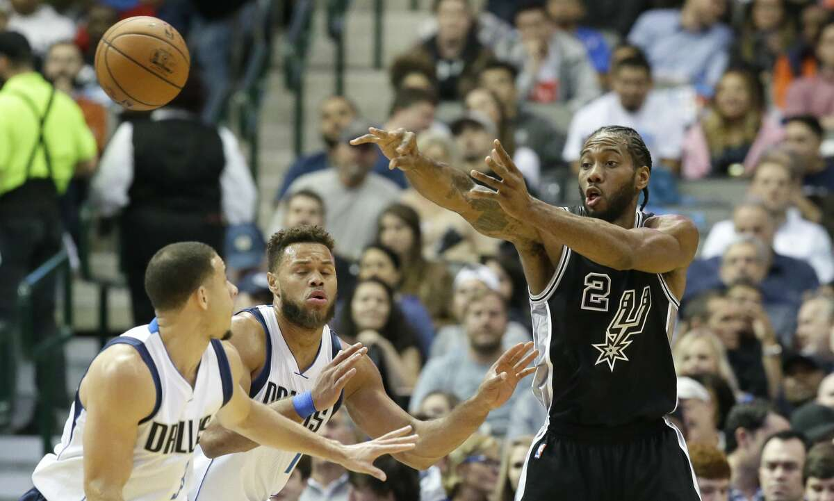 San Antonio Spurs forward Kawhi Leonard (2) passes against Dallas Mavericks defenders Justin Anderson (1) and Seth Curry (30) during the first half of an NBA basketball game in Dallas, Wednesday, Nov. 30, 2016. (AP Photo/LM Otero)