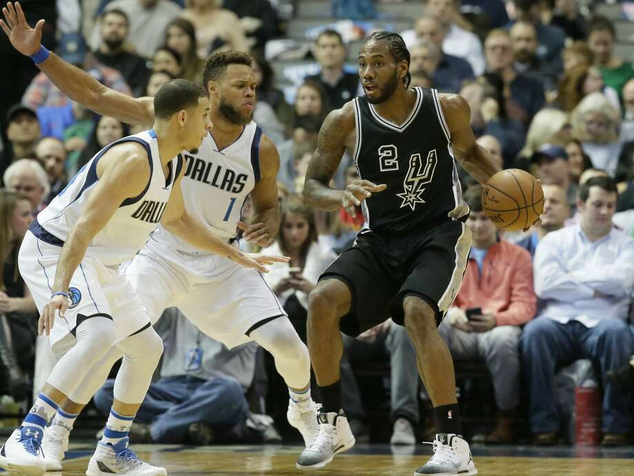 San Antonio Spurs forward Kawhi Leonard (2) dribbles against Dallas Mavericks defenders Justin Anderson (1) and Seth Curry (30) during the first half of an NBA basketball game in Dallas, Wednesday, Nov. 30, 2016. (AP Photo/LM Otero) Photo: LM Otero/Associated Press