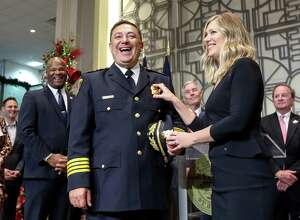 Police Chief Art Acevedo, third from left, jokes with his wife Tanya Acevedo, whom he said stuck him while pinning his badge on, after he was sworn in, Wednesday, Nov. 30, 2016, in Houston. ( Jon Shapley / Houston Chronicle )
