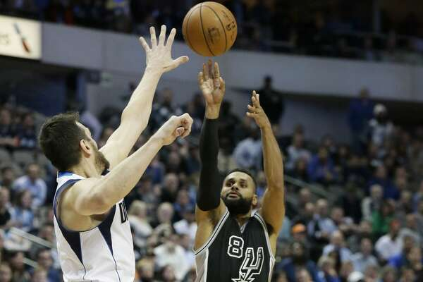 San Antonio Spurs guard Patty Mills (8) shoots a three pointer against Dallas Mavericks center Andrew Bogut (6) during the second half of an NBA basketball game in Dallas, Wednesday, Nov. 30, 2016. The Spurs won 94-87. (AP Photo/LM Otero)