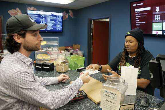 Justin Port, left, pays budtender Kysa Butler for his cannabis in cash at Magnolia Wellness, a medical marijuana dispensary in Oakland, Calif., on Wednesday, November 30, 2016. Like many businesses working in the cannabis industry, Magnolia Wellness has to deal with a lack of access to formal banking services. However, a special bank may soon open up in oakland to fill this void.