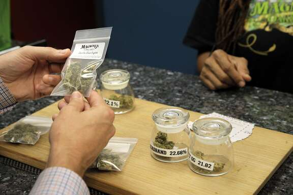 Justin Port checks out several different marijuana varieties at Magnolia Wellness, a medical marijuana dispensary in Oakland, Calif., on Wednesday, November 30, 2016. Like many businesses working in the cannabis industry, Magnolia Wellness has to deal with a lack of access to formal banking services. However, a special bank may soon open up in oakland to fill this void.
